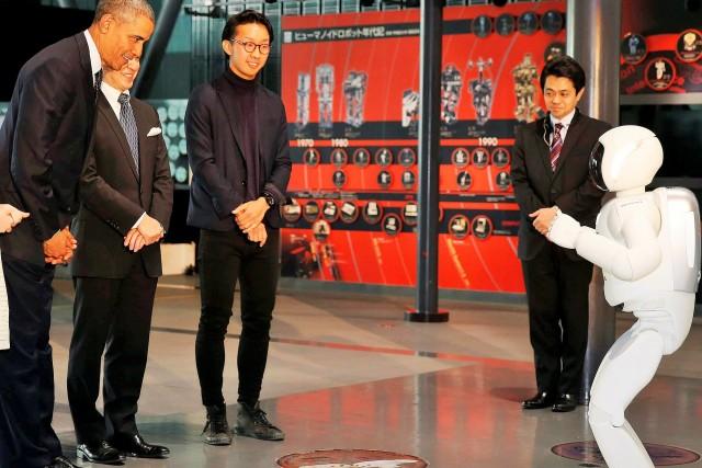 "U.S. President Barack Obama bows to ""Asimo"" the robot while visiting Miraikan in Tokyo"